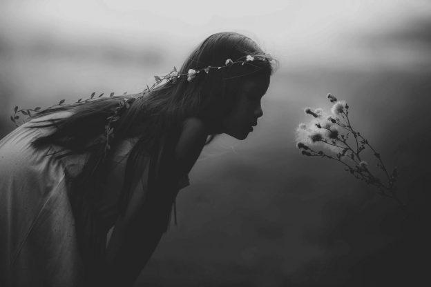 Schwarz-weiß Bild auf dem ein Kind und eine Blume zu sehen sind