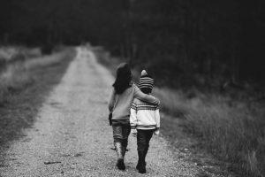 Kinder laufen umarmt einen Weg entlang