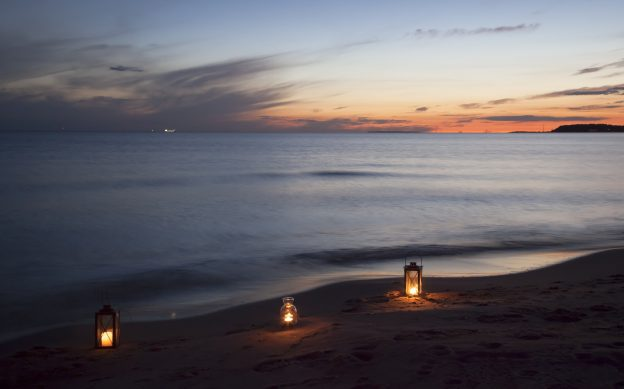 Drei Kerzen sind bei Sonnenuntergang am Strand aufgestellt