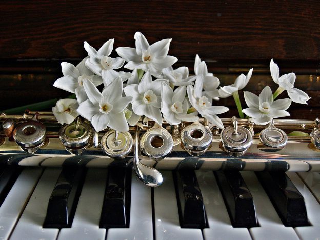 Ein Blumengesteck liegt auf einer Klarinette, die auf einem Klavier abgelegt wurde.