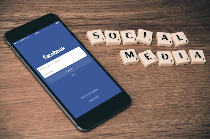 Smartphone mit der Facebook-App, Scrabble-Buchstaben ergeben Social Media als Text