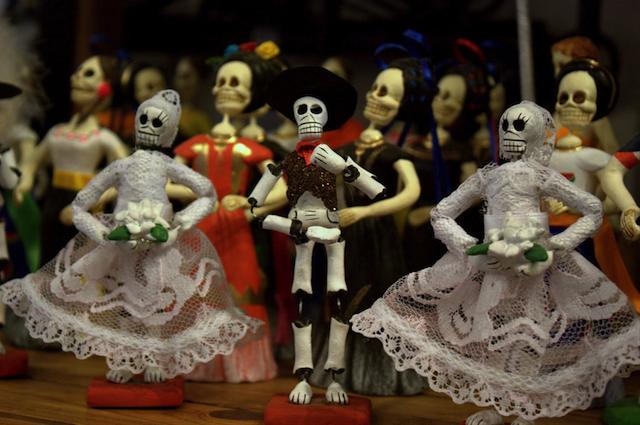 Weibliche und männlich gekleidete Totenkörper stehen zum Tanz beim Día de los Muertos bereit.