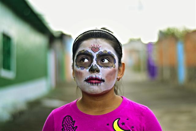 Ein anlässlich des Día de los Muertos geschminkte Mädchen schaut mit den Augen zur Seite.