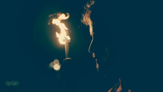 Ein Mann steht im Schatten, angeleuchtet von der Flamme