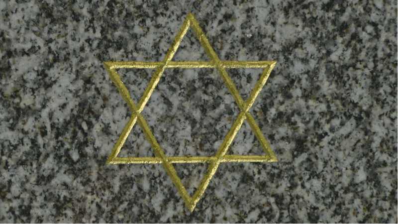 Ein goldenfarbiger Davidstern ist auf einem Mamorgrabstein eingemeißelt.